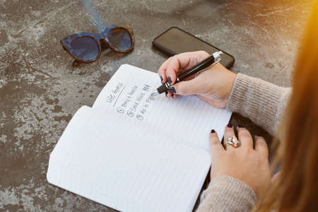 Young female writes her life goals with a pen and paper.  Sunglasses and cell phone are on the table