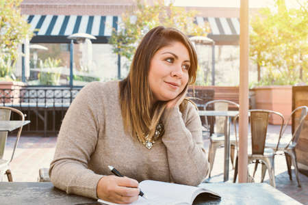 View of Young Latina having aspirations and writing down her goals