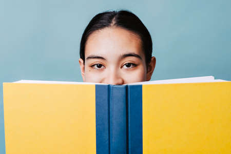 Young Teenage girl smiles behind her book in happiness with the content