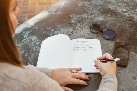 Profile of a female millennial writting down her life goals