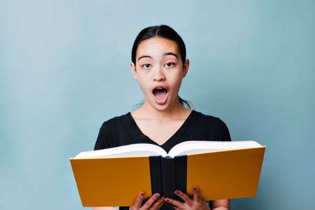 Young female student reads textbook and has a shocked expression