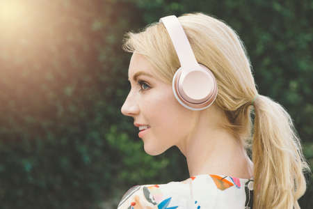 A white female millennial has an inspirational and happy moment while listening to music on pink headphones