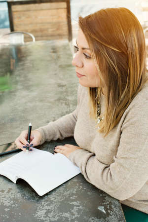 View of a young female woman looking and pondering what to write in her journal.  Inspiration and hope Stock Photo