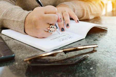 View of female hands writing her life goals in a journal Stock Photo