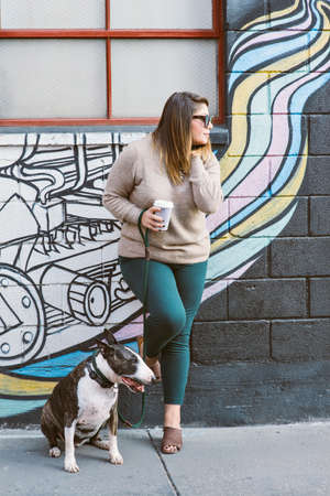A female and her pet Bull Terrier wait in a alley.  Girl is holding a coffee  cut while looking to the side
