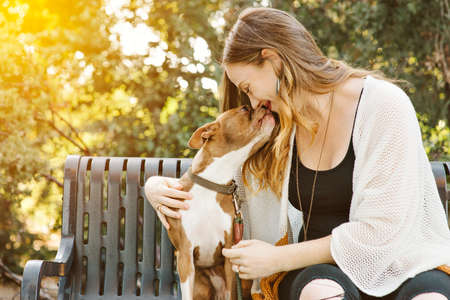 Caucasian female with brown hair kisses her pet dog on a park bench.  Mans best friend.  Loving relationship