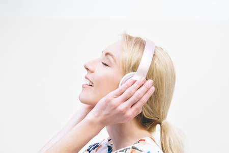 Blond female millennial listens to music on headphones and is inspired against a plain background
