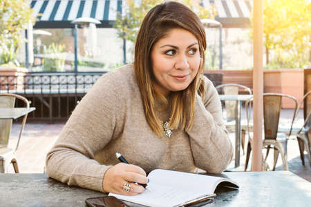Pretty Hispanic Woman Writes in a Journal at an Outdoor Cafe and Smiles in Warm Light Stock Photo