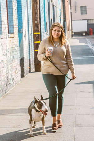 Millennial Woman Walks her Pet Dog in an Alleyway in an Urban Setting with a Coffee Cup