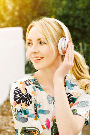 Millennial Female listens to music on her headphones and has a big smile happy and having fun Stock Photo