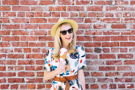 Young white female eats an ice cream cone on a summer day with sunglasses and a fedora