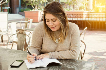 Young latina writes down her goals in a journal outdoors in a cafe