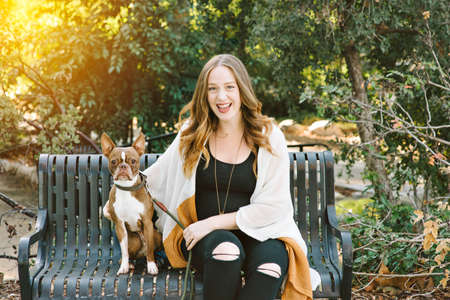 A white female sits next to her dog on a park bench with the sun setting behind her very happy