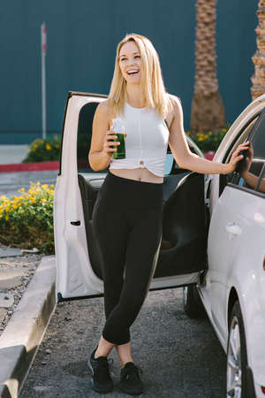 Blond girl laughs as she holds a water bottle after her work out by her car