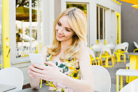 A blond woman looks at her cell phone and smiles at an outdoor cafe in the summer