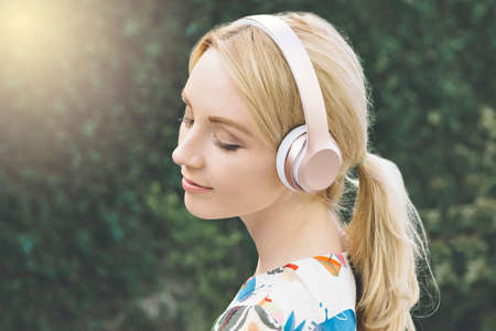 Young white woman has her eyes closed and is moved by listening to music on her headphones