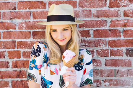 Young white woman is eating an ice cream cone in front of a brick wall Stock Photo