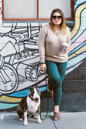 View of a woman with a coffee cup while standing next to her pet dog Stock Photo