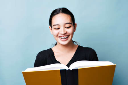 Teen girl laughs at a school book with large smile against a blue background