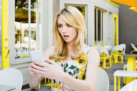 Girl with shocked expression looks at her cell phone at an outdoor cafe