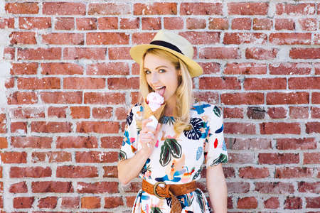 Pretty young white girl licks an ice cream cone with a fedora hat in the summer