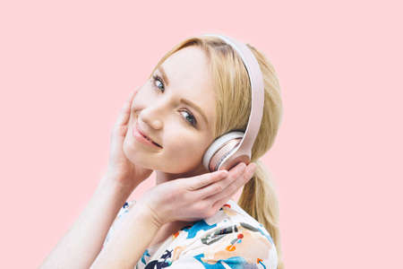 Front view of a young Caucasian girl with headphones on and listening to music on a pink background Stock Photo