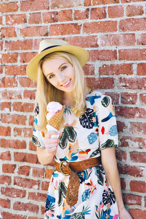 Cute trendy girl standing outdoors with an ice cream cone and a fedora hat