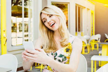 Front view of a young blond girl looking at her phone and laughing while outdoors Stock Photo