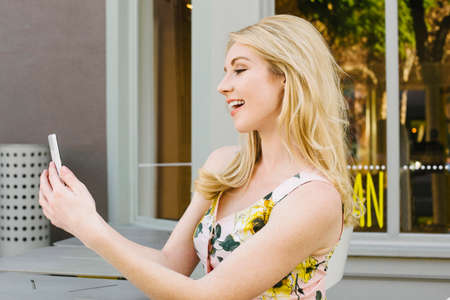 Side view of a blonde girl texting and smiling at her screen Stock Photo