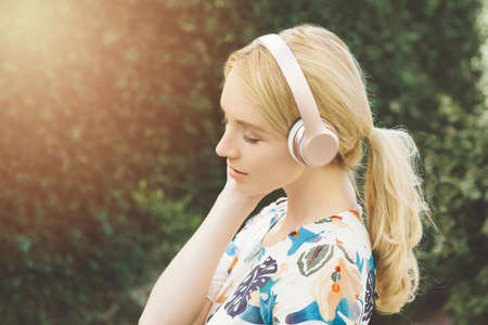 View of young Caucasian woman listening to music and being inspired in an outdoor setting Stock Photo