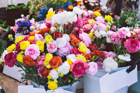 Buckets of beautiful and colorful flower bouquets are for sale at a farmers market stall Stock Photo