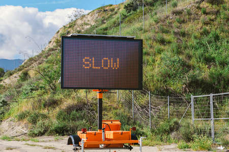 A Slow Sign on an electronic panel on the side of a freeway with a hill and clouds in the sky Stock Photo