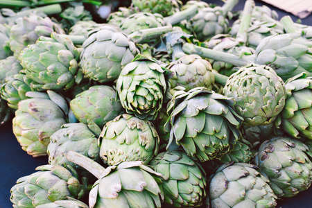 Green artichokes laying in a bunch on a table for sale at a farmers market