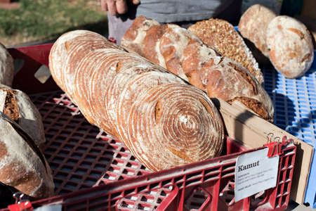 Rustic kamut bread is sold in a market stall at an outdoor farmers market
