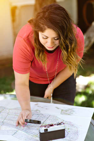 A young Hispanic woman reviews her travel destinations on a map with a magnifying glass and a camera Stock Photo