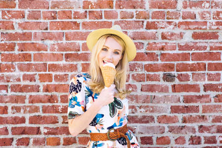 Hip young female with a fedora hat licks an ice cream on a hot day Stock Photo