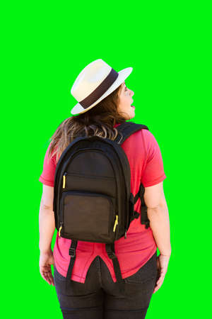 A traveling woman on green background walks away while looking at something to her right Stock Photo
