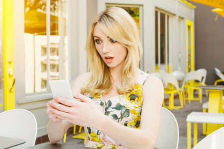 Pretty woman is shocked at photo or text that is on her smart phone at an outdoor cafe Stock Photo