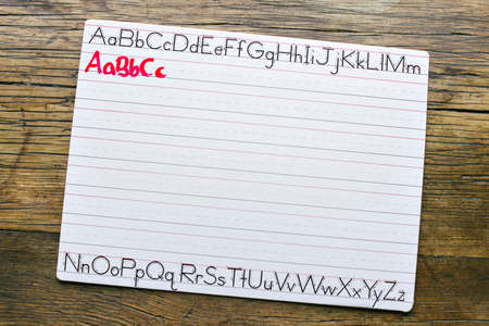 Top view of a white penmanship board with the letters ABC written in red marker by a child Banco de Imagens