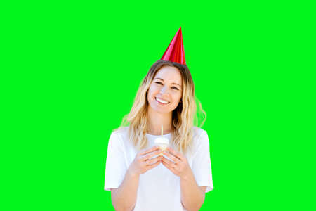 Young Caucasian girl smiles while she holds a birthday cupcake and wearing a birthday hat