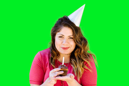 Smiling woman holds a birthday cupcake on green screen Stock Photo