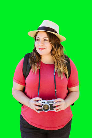 Latina millennial woman holds an old camera while travelling and wearing a fedora