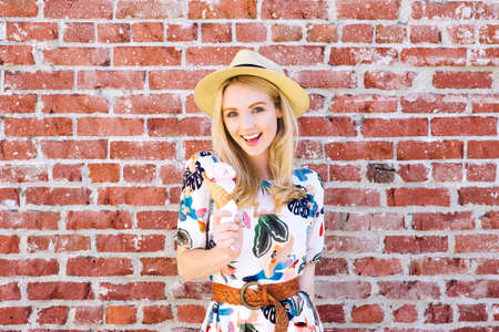 Beautiful smiling young woman stands by a brick wall with an ice cream in her hand in the summer