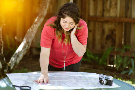 Young Hispanic woman plans her road trip on a map of the United States with a camera
