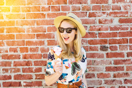 Millennial girl holds and ice cream while smiling in the summer time with fedora, shades and warm light