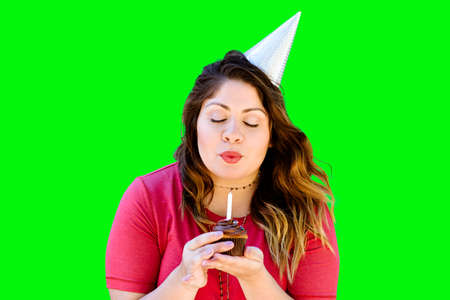 Woman blowing out her birthday candle on a chocolate cupcake on green screen