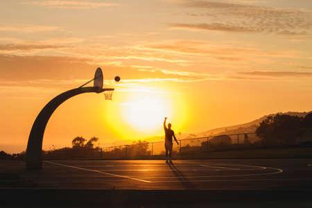 Male plays basketball alone while the sunsets behind him outdoors Stock Photo