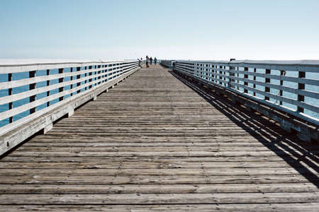 Blue skies and a long wooden pier in San Simeon, CA