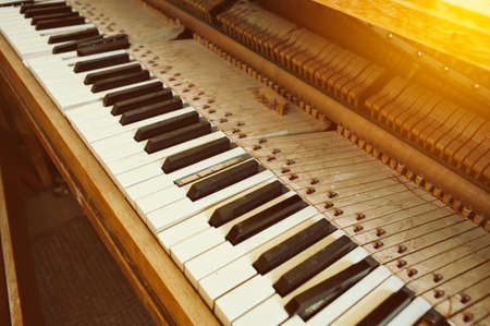 Angled view of old piano with broken keys and dust in warm lighting