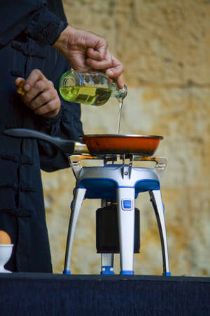 Chef pouring olive oil into a pan photo